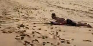 Jovem usa prancha de Skimming para deslizar de uma duna até ao mar
